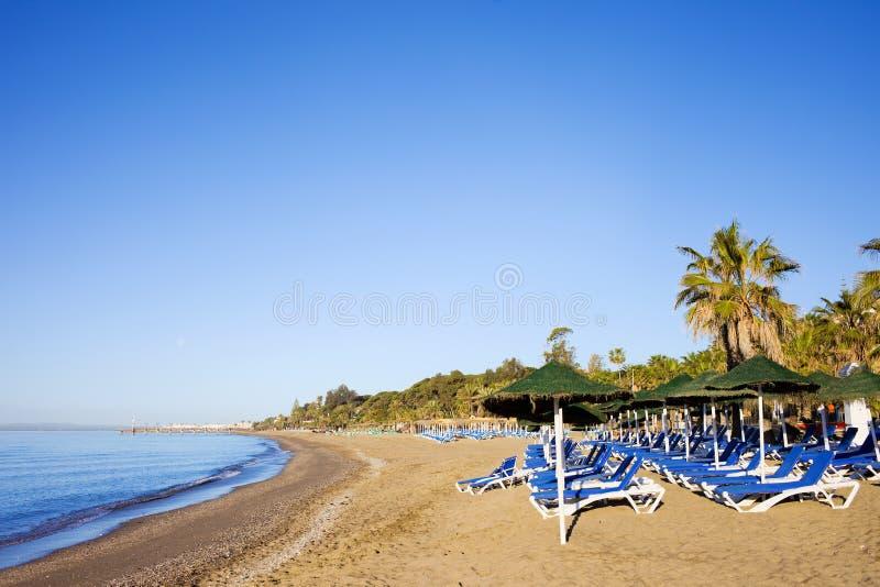 strandloungersmarbella sandig sun fotografering för bildbyråer