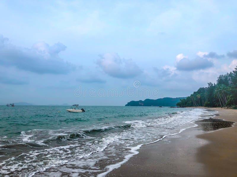 Strandmening met boot in zonsondergangtijd stock foto's