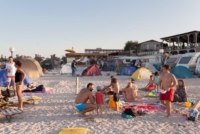 Strandoverzicht - toeristen die van de laatste stralen van de zon genieten stock afbeeldingen