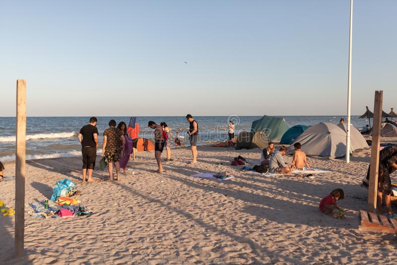Strandoverzicht Toeristen in een zonsonderganglicht stock fotografie