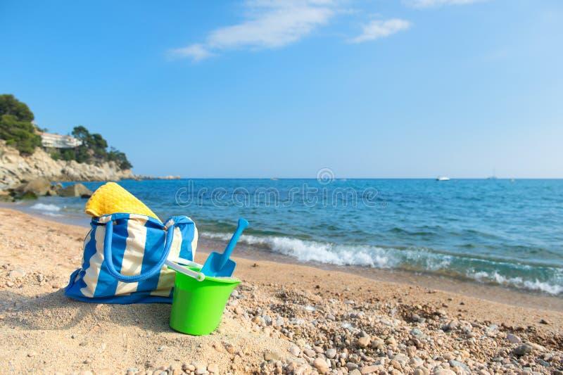 Strandpåse och leksaker på stranden royaltyfria bilder