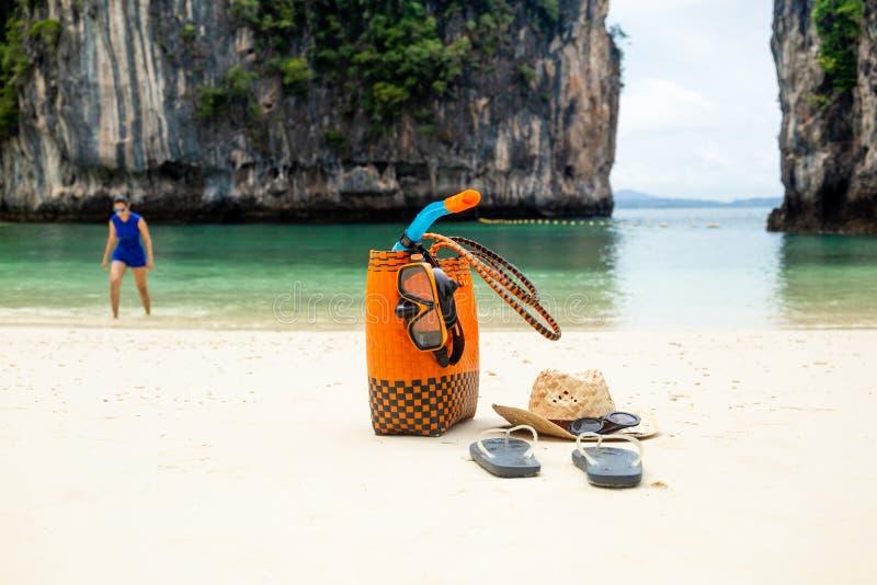 Strandpåse- och lopptillbehör med kvinnan i suddighetsbakgrund på semester arkivfoto