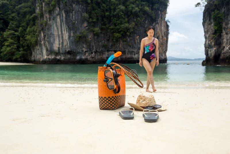 Strandpåse- och lopptillbehör med kvinnan i suddighetsbakgrund på semester arkivbilder