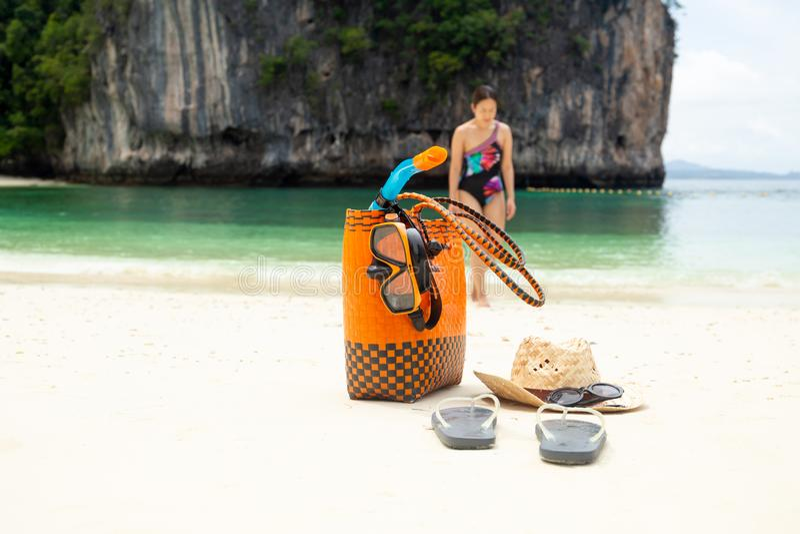 Strandpåse- och lopptillbehör med kvinnan i suddighetsbakgrund på semester royaltyfria bilder