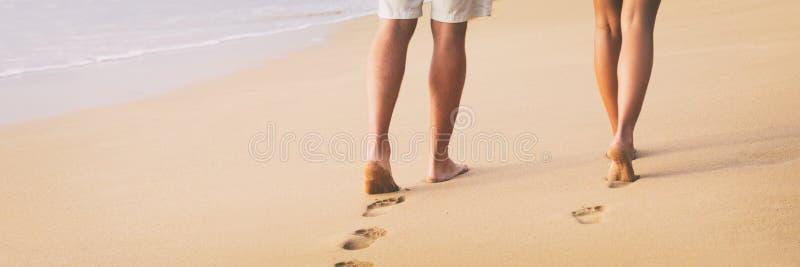 Strandpaar die blootvoets op zand bij de banner van de de wittebroodswekenreis van de zonsonderganggang lopen - vrouw en man die  royalty-vrije stock foto