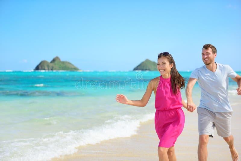 Strandpaar het gelukkige lopen hebbend pret op Hawaï stock foto