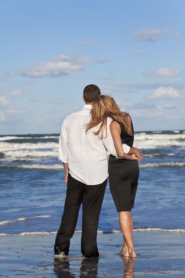 strandpar som omfamnar manromantikerkvinnan royaltyfria bilder