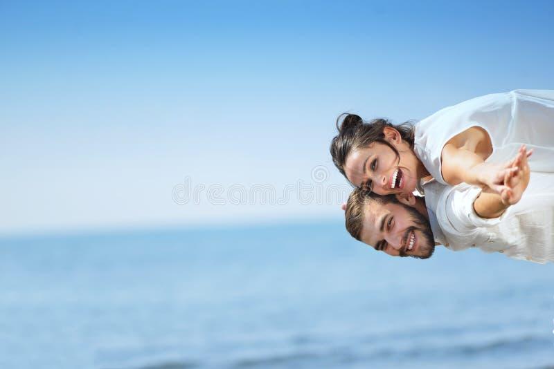 Strandpar som skrattar förälskad romans på loppbröllopsresasemester arkivbild