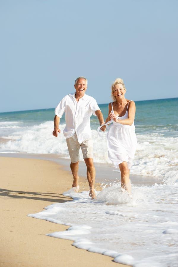 strandpar som tycker om feriepensionärsunen royaltyfria foton
