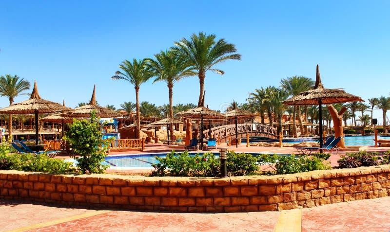 Strandparaplu's en sunbeds op de pool stock afbeelding