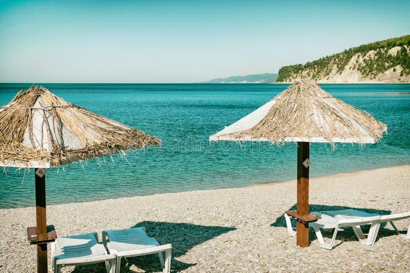 Strandparaplu's en zonbedden op de oceaan stock afbeelding