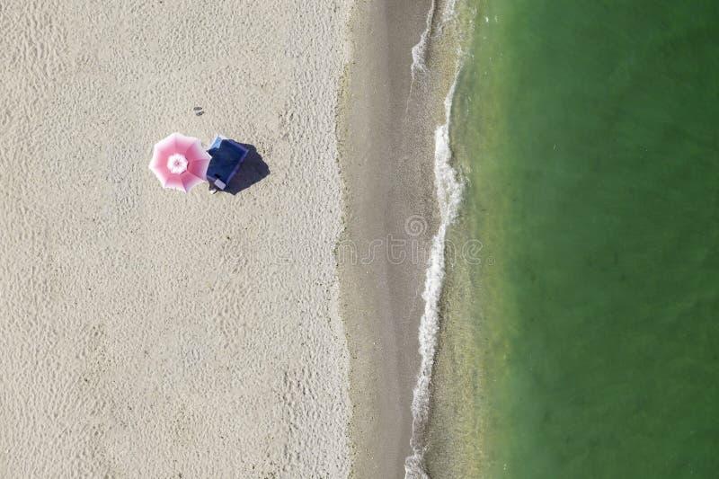 Strandparaply bara på kusten Top besk?dar flyg- sikt Guld- sand och gröna havvågor Sikt för fågelöga på stranden Umbrel royaltyfria foton