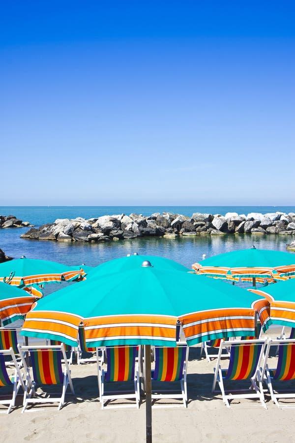 Strandparaply i en italiensk kustlinje - bild med kopieringsutrymme royaltyfri fotografi