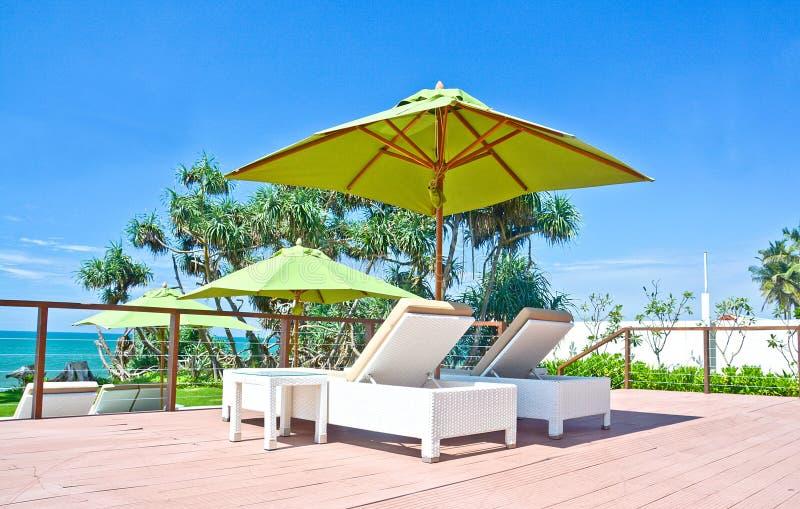 Strandparaply och Sunbath platser i ett tropiskt hotell som lokaliserade i Costal område Negambo, Sri Lanka royaltyfria bilder