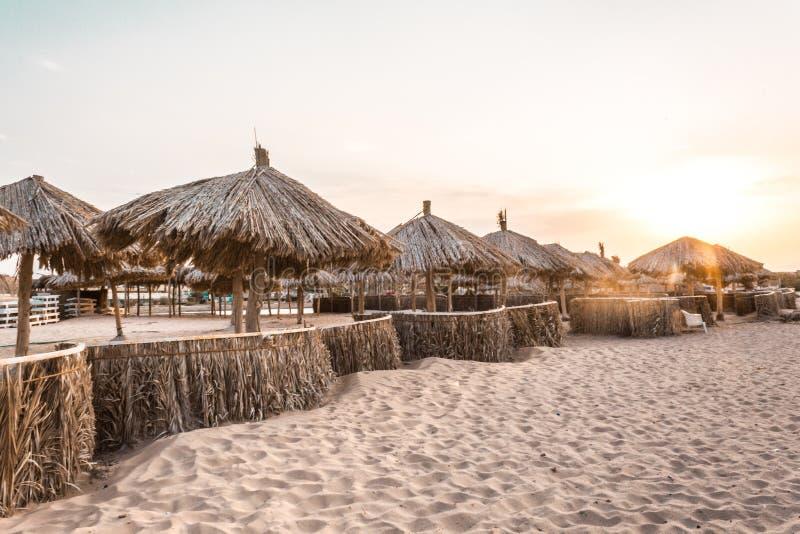 Strandparaplyer från naturliga material vid havet på sanden arkivfoto