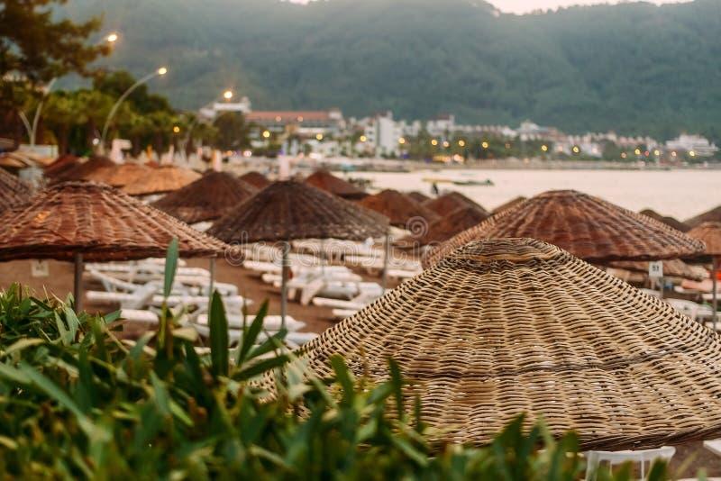 Strandparaplyer och sunbeds vid havet på solnedgången, Turkiet royaltyfri bild