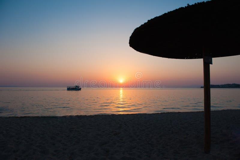 Strandparaplyer på solnedgången, med solsängar, varm solnedgång Mjuka havsvågor och bubblor på stranden med solnedgånghimmelbakgr royaltyfri foto