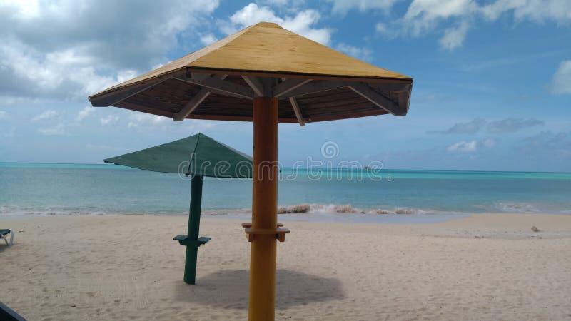 Strandparaplyer, sand och turkosvatten arkivbilder