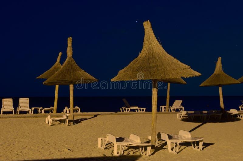 Strandparaplyer, vardagsrumstolar, natt fotografering för bildbyråer