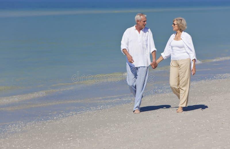 strandparet hands den lyckliga holdingen högt gå arkivfoto