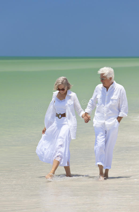 strandparet hands den lyckliga holdingen högt gå royaltyfria bilder