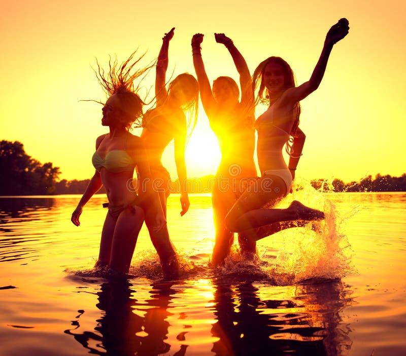 strandparti Lyckliga flickor i vatten över solnedgång fotografering för bildbyråer