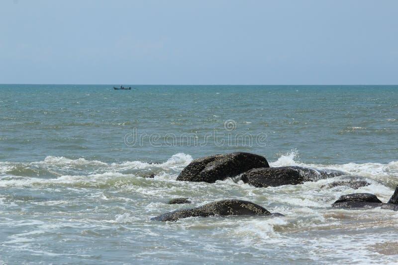 Strandrotsen met een vissenboot stock foto's