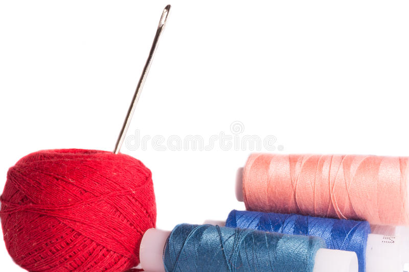 Strands of red, blue, black and cherry colors with needle stock photos