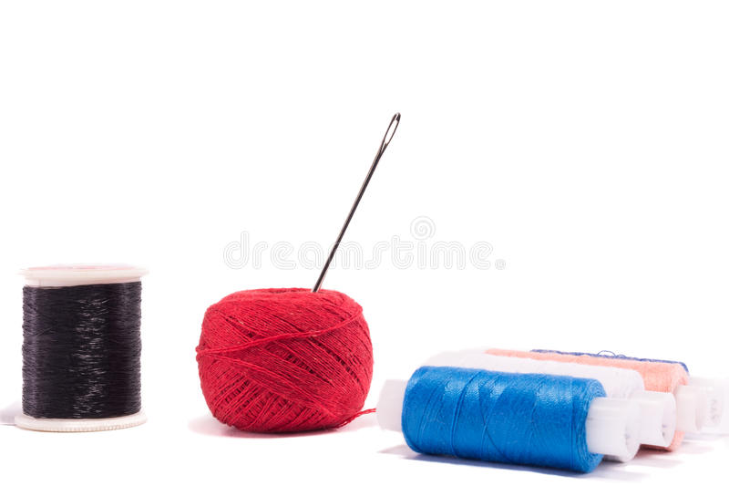 Strands of red, blue, black and cherry colors with needle royalty free stock photos