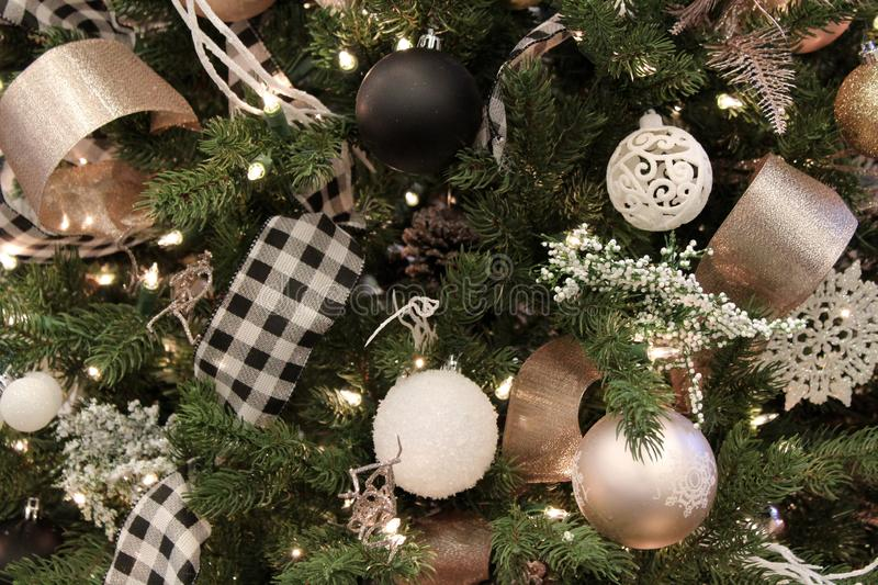 Themed Christmas tree covered with childhood memories, baubles, ribbon, and strands of twinkling lights. Strands of twinkling lights woven throughout holiday stock photo