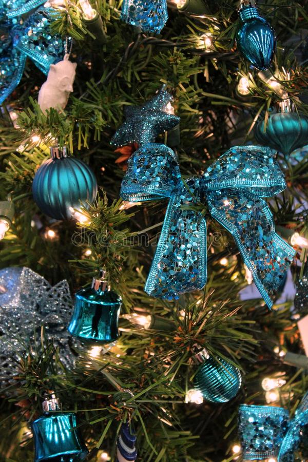 Blue-themed Christmas tree covered with childhood memories, baubles, ribbon, and strands of twinkling lights throughout. Strands of twinkling lights woven stock image