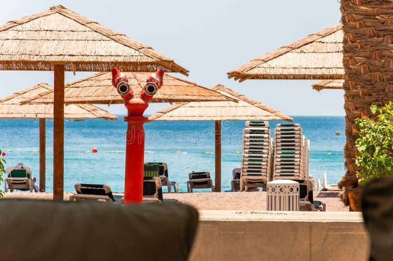 Strandsamenstelling, rode hydrant fireplug als gezicht van één of ander schepsel kijken, de zomerparaplu's, bos van chaise zitkam royalty-vrije stock afbeeldingen