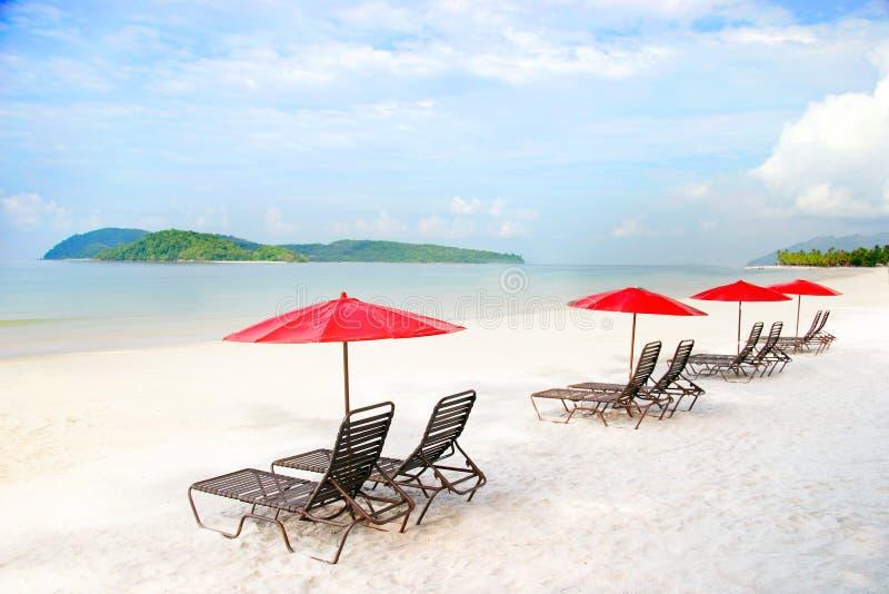 strandsanden placerar paraplyer arkivbilder