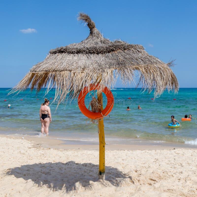 Strandschirm mit lebensrettender Ausrüstung auf den Hintergrundleuten spielen im Wasser lizenzfreies stockbild
