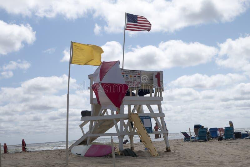 Strandshoreline med livräddaretornet med paraplyet för sol för flaggaräddningsaktionbräden arkivfoton