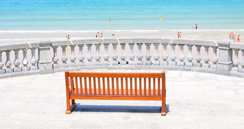 Strandsikt med den härliga träbänken royaltyfri fotografi