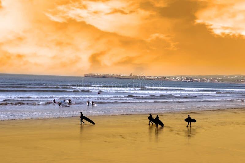 strandsolnedgångsurfarear som går barn royaltyfria foton