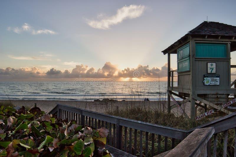 Strandsoluppgång med livräddaretornet royaltyfri fotografi