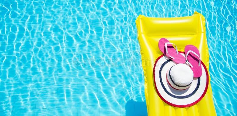 StrandSommerferienhintergrund Aufblasbare Luftmatraze, Flipflops und Hut auf Swimmingpool Gelbes lilo und Sommerzeit stockfoto