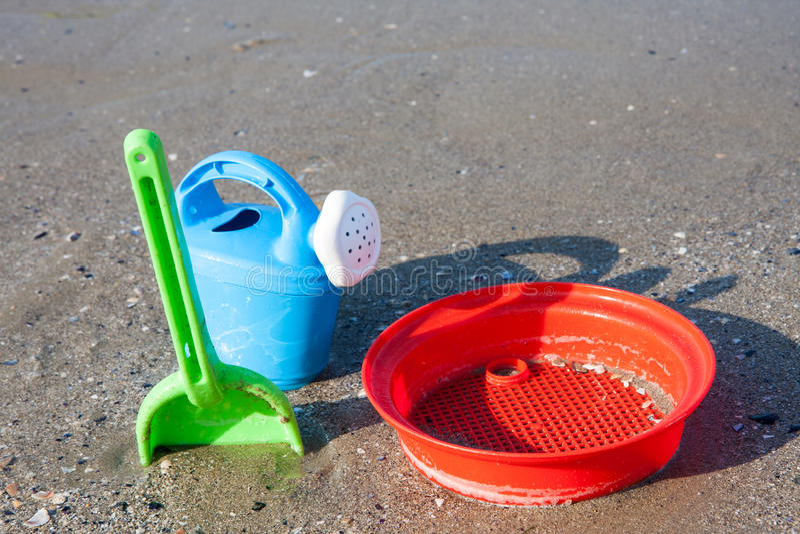 Strandspeelgoed in het zand en het overzees stock afbeeldingen
