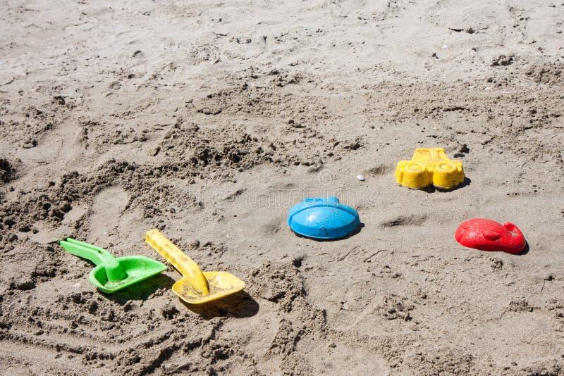 Strandspeelgoed in het zand en het overzees stock foto's