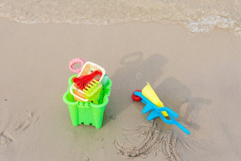 Strandspeelgoed op het zandstrand met spadeschop voor de kinderen stock foto's