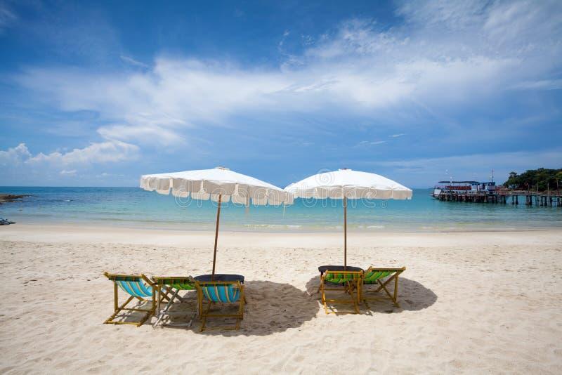 Strandstühle auf dem weißen Sandstrand lizenzfreie stockfotografie