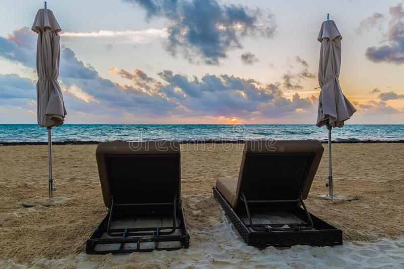 Strandstühle bei Sonnenaufgang stockbild