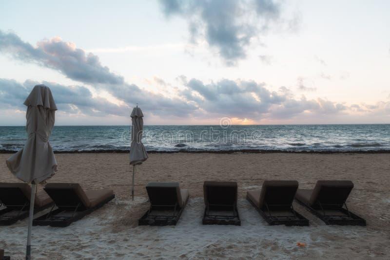 Strandstühle bei Sonnenaufgang lizenzfreie stockfotografie