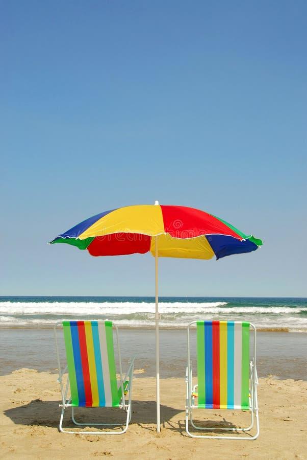 Strandstühle und -regenschirm stockfoto