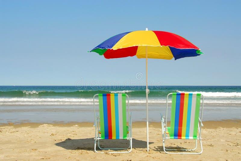 Strandstühle und -regenschirm lizenzfreies stockfoto
