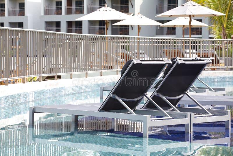 Strandstühle und Regenschirmseitenswimmingpool stockfotos