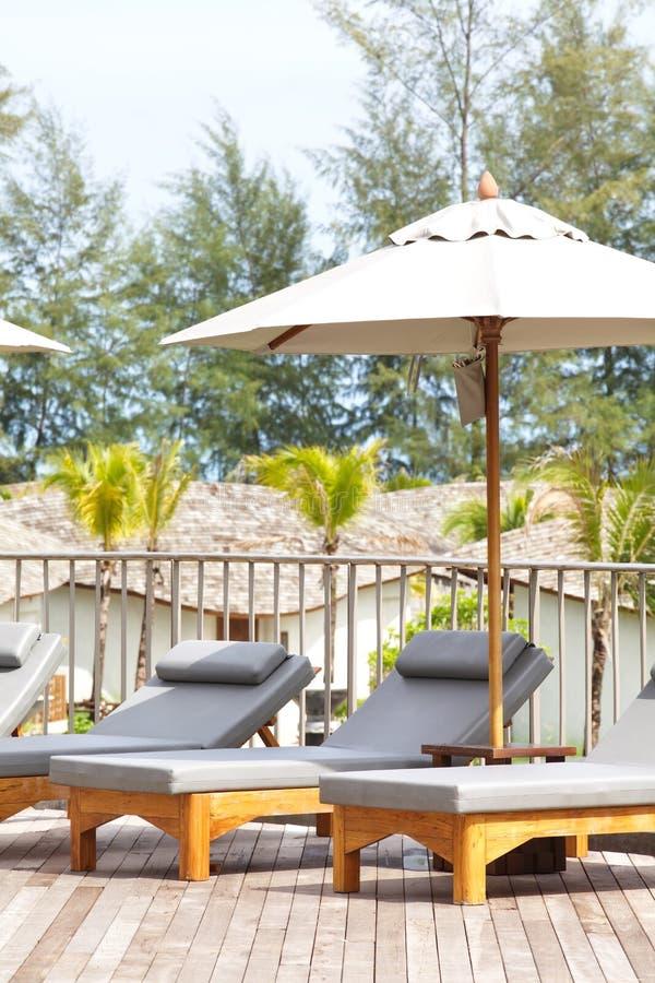 Strandstühle und Regenschirmseitenswimmingpool lizenzfreies stockfoto
