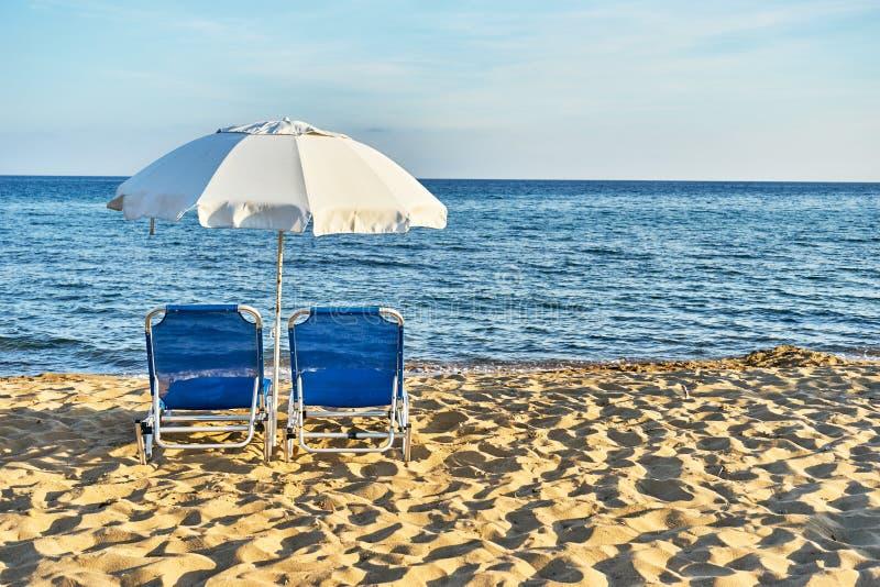Strandstolar med paraplyet och den härliga stranden på en solig dag arkivbild